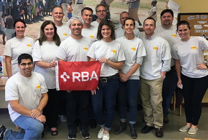 Photo of RBA emplyees volunteering and holding RBA flag