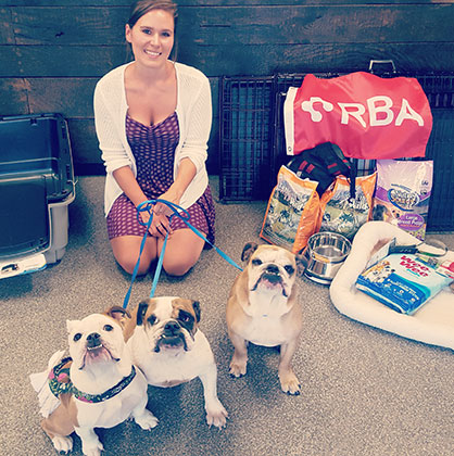RBA female employee with three bulldogs donating items to Secondhand Hound